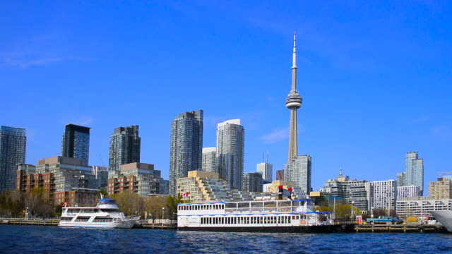 toronto, canada: urban skyline with cn tower and boats in the waters of lake ontario - stationary stock videos & royalty-free footage