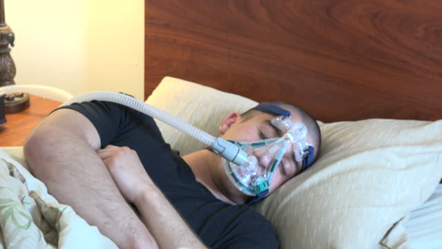 toronto, canada, young adult suffering from sleep apnea, zoom out - sleep apnea stock videos and b-roll footage
