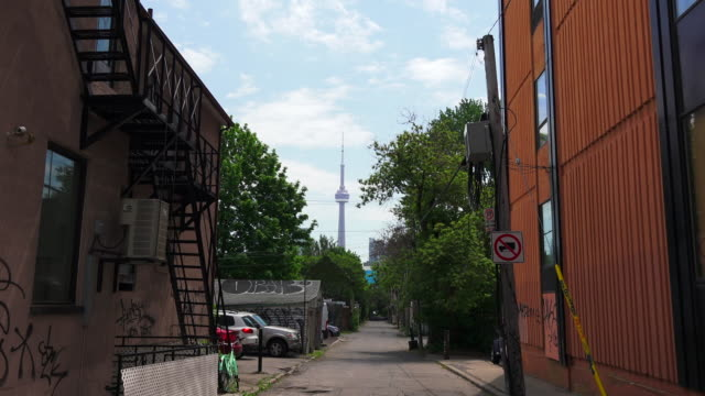 toronto, canada: zoom cn tower from college street in downtown district. architectural contrast of old red brick building and the modern telecommunication tower which is a famous tourist attraction - famous place stock videos & royalty-free footage