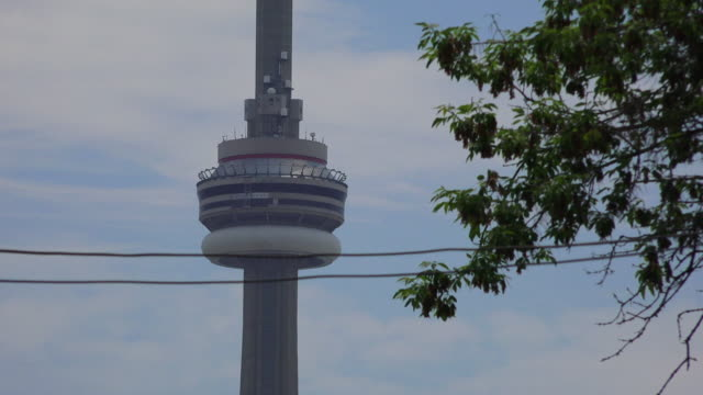 Toronto, Canada: Zoom CN Tower from College street in downtown district. Architectural contrast of old red brick building and the modern telecommunication tower which is a famous tourist attraction