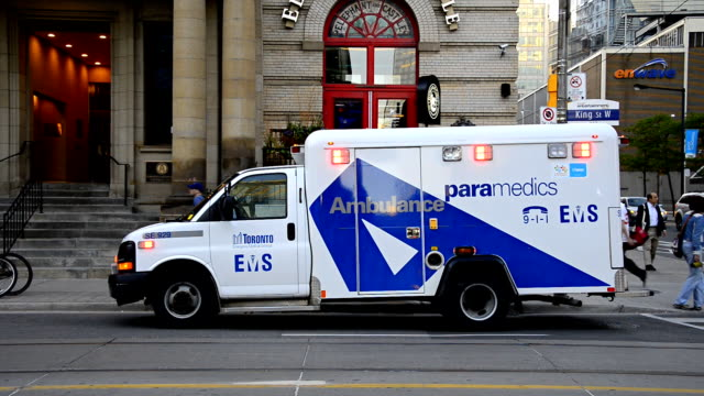 Toronto EMS ambulace with lights on in downtown