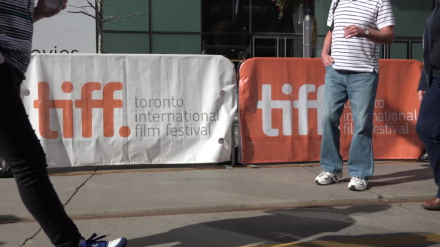 pedestrian walking in front of tiff signage in the new festival street festival street is the temporary name given to king street west during the... - toronto international film festival stock videos and b-roll footage