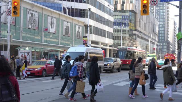 vídeos y material grabado en eventos de stock de toronto, ontario, canada-april 10, 2014: establishing shot of pedestrians and traffic in the yonge-dundas square area. a vintage ttc streetcar is... - lugar famoso local