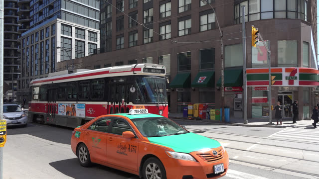 toronto, ontario, canada-april 10, 2014: panning a vintage ttc overhead cable car or streetcar which has a pan american games advertisement on the... - taxi stock videos & royalty-free footage
