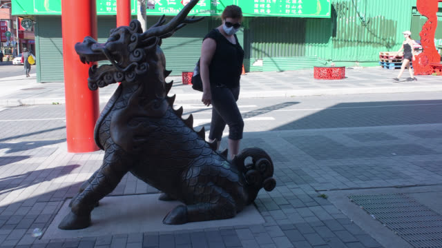 stockvideo's en b-roll-footage met toronto, ontario, canada-august 14, 2020: a female tourist examines a metallic statue of a dragon in chinatown. the sculpture is part of the chinese... - hoog contrast