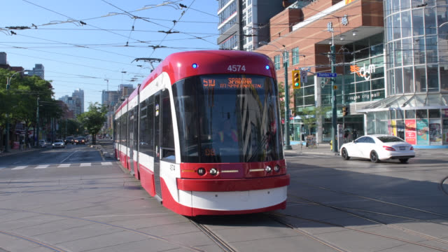 toronto, ontario, canada-august 14, 2020: a new bombardier flexity outlook ttc streetcar drives in the iconic district named 'chinatown'. to the... - major road bildbanksvideor och videomaterial från bakom kulisserna