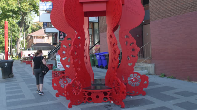 vídeos y material grabado en eventos de stock de toronto, ontario, canada-august 14, 2020: a tourist walks by red decorative figures with seats for people to enjoy a rest or some food. the ornament... - lugar famoso local