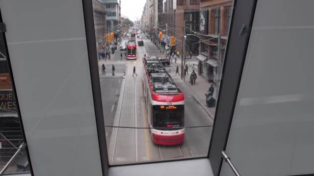 toronto, ontario, canada-august 24, 2019: the camera looks through the glass towards queen street west where a ttc streetcar drives. located in the... - local landmark stock videos & royalty-free footage