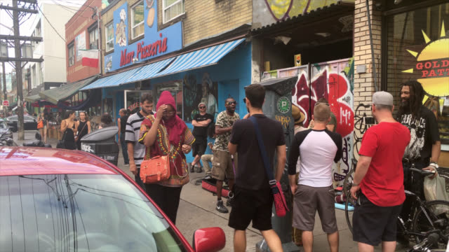 toronto, ontario, canada-august 25, 2019: left pan showing the general atmosphere in kensington market which is a local landmark and a tourist... - luogo d'interesse locale video stock e b–roll