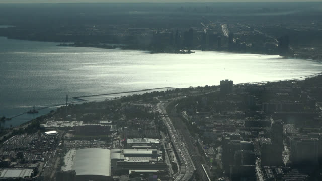 stockvideo's en b-roll-footage met toronto, ontario, canada-circa july 1, 2017: backlit afternoon image of the urban skyline in the waterfront of the city. the image is a tourist point... - ontariomeer