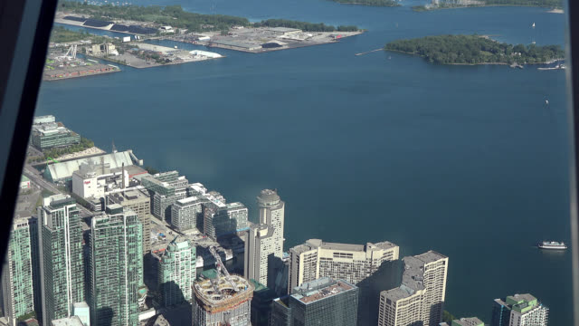 stockvideo's en b-roll-footage met toronto, ontario, canada-circa july 1, 2017: tilt-up showing the waterfront of the city by the lake ontario. the image is a tourist point of view... - ontariomeer