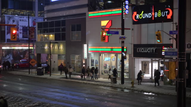 toronto, ontario, canada-december 18, 2019: high angle view of yonge street showing diverse business signs suach as 7 eleven, panera bread, and round... - local landmark stock videos & royalty-free footage