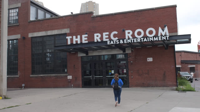 toronto, ontario, canada-july 15, 2020: a tourist walks towards the entrance of the rec room which is a famous place across the cn tower. the place... - luogo d'interesse locale video stock e b–roll