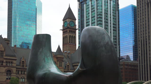 toronto, ontario, canada-october 8, 2019: zoom out from the old city hall clock and bell-tower towards 'the archer' abstract sculpture by henry moore... - henry moore stock videos & royalty-free footage