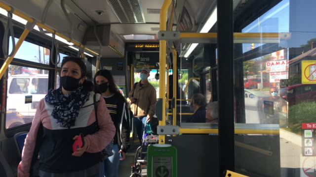 toronto, ontario, canada-september 20, 2020: real people wearing protective face coverings inside of a ttc or toronto transit commission bus. during... - epidemiologia video stock e b–roll