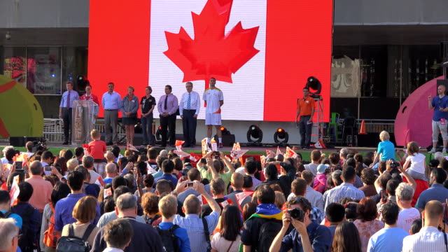 toronto personalities and crowd sign the national anthem during torch relay celebration in nathan phillips square one day before the start of the... - パンアメリカンハイウェイ点の映像素材/bロール