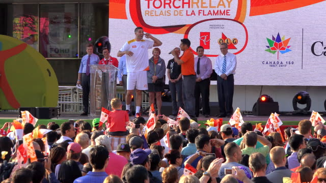 toronto raptor greivis vazquez carried the torch to the stage during the pan am torch relay celebration at nathan phillips square the main stage for... - パンアメリカンハイウェイ点の映像素材/bロール