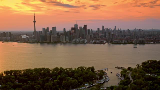 antenna skyline di toronto attraverso l'inner harbour al tramonto - ontario canada video stock e b–roll