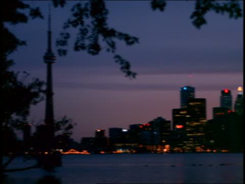 pan toronto skyline across water at dusk / toronto, canada - anno 1999 video stock e b–roll