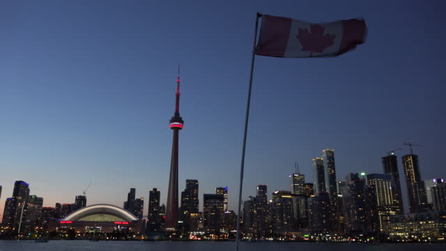 toronto skyline at night from tourist cruise, canadian flag waving in ship - bandiera del canada video stock e b–roll