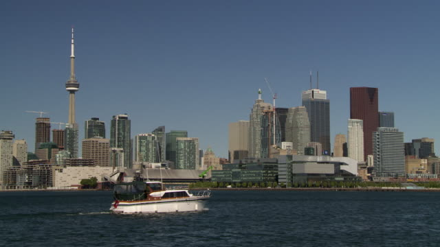 Toronto Skyline taken in Ontario Canada.  Lake Ontario spans in front and the CN tower is featured to the left.  A personal yacht travels through the frame.
