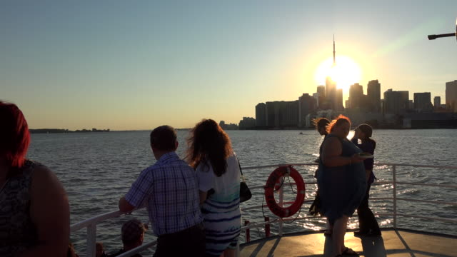 tourist group enjoying a cruise in lake ontario they are moving toward the city skyline with the cn tower and a beautiful sunset in the sky - lake ontario bildbanksvideor och videomaterial från bakom kulisserna