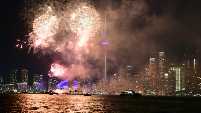 Toronto skyline with Fireworks of Canada Day. Point of view from ship in Lake Ontario at night