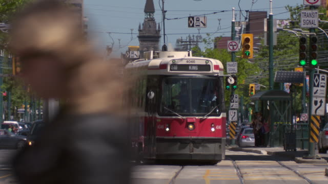 Toronto Streetcar trolley makes a left turn on Spadina and Adelaide West.  The Trolley stations are featured as well as the traffic nearby.