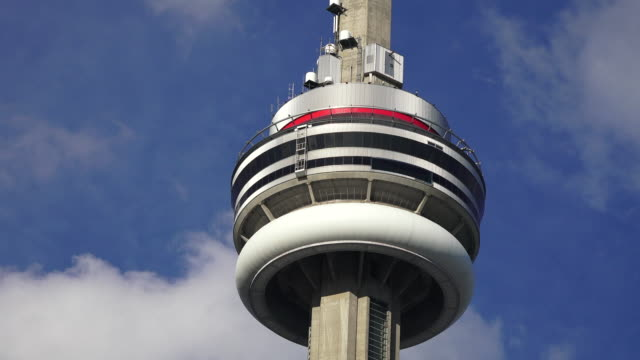 Toronto,Canada: CN Tower in clear blue sky. Time lapse of some clouds passing behind the main pod