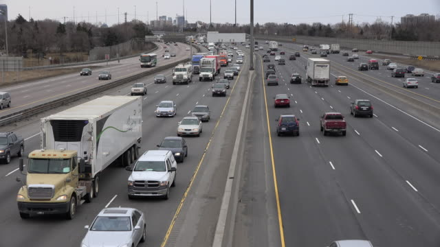 toronto,canada: highway 401 crossing through the city, its traffic in non rush hour during daytime - ontario canada stock videos and b-roll footage