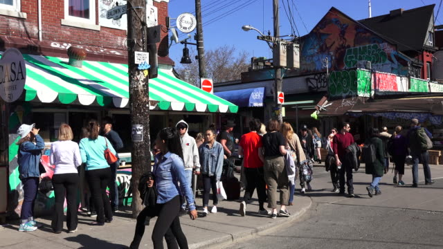 vidéos et rushes de toronto,canada: kensington market everyday lifestyle and routine. pedestrians in the street. the neighborhood in the downtown district is a national historic site of canada - toronto