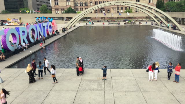 toronto,canada: nathan phillips square with 3d sign in the new city hall town square. the famous place is a tourist attraction in the canadian city capital of the province of ontario. city outdoors lifestyle during day - 文字点の映像素材/bロール