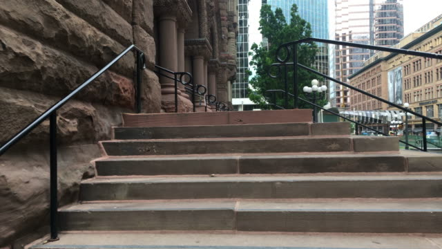 Toronto,Canada: Old City Hall. Richardsonian Romanesque Revival architecture. Point of view while walking up the stairs at the entrance. The famous place is tourist attraction in the downtown district of the Canadian city capital of province of Ontario