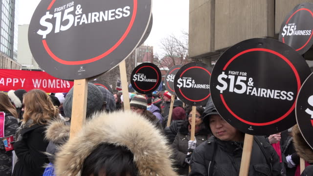 social struggles international women's day signs demanding a minimum wage of $15 dollars an hour marchers in the downtown district of the canadian... - internationaler frauentag stock-videos und b-roll-filmmaterial