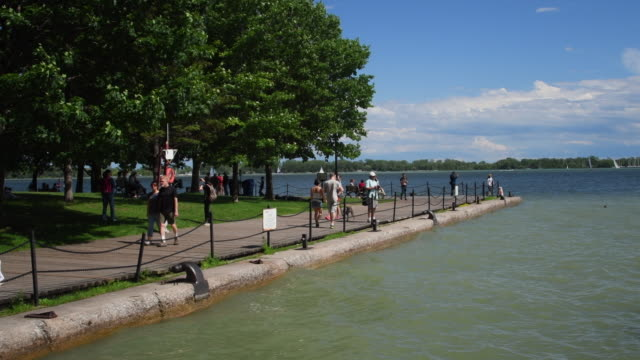 toronto,canada: waterfront harbourfront with higher than normal water levels. real people lifestyle in a beautiful summer day. recreation in the downtown district of the canadian city - waterfront stock videos & royalty-free footage