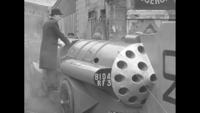 vídeos de stock, filmes e b-roll de torpedo car moves with other cars on paris street as all approach camera / torpedo car moves in reverse as man in overcoat and bowler hat stands on... - inventor