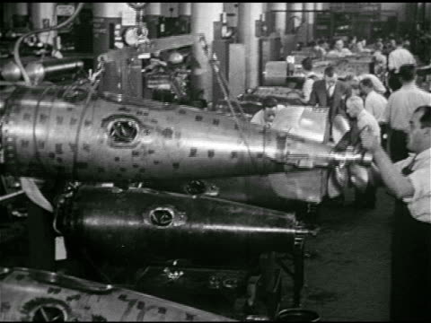vídeos de stock, filmes e b-roll de torpedoes being assembled lifting on crane turning on lathe vs testing torpedo tubes opening closing doors moving tube w/ crane in us navy warehouse... - 1943