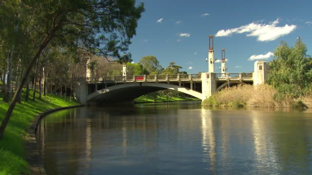 Torrens River waters edge looking towards King William Bridge with green grass river bank