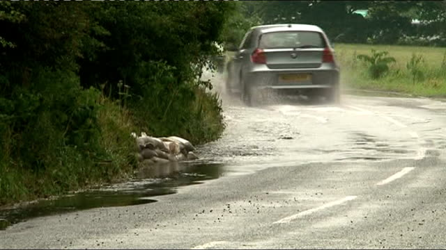 torrential rain and floods across england and wales; northumberland: bv car driving along road, spraying up sitting water downed telegraph pole lying... - northumberland video stock e b–roll