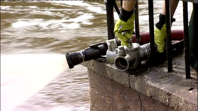 Torrential rain causes flooding in Northern England EXT / DAY Firefighter setting up pump in flood water Firefighter in flooded basement of local...
