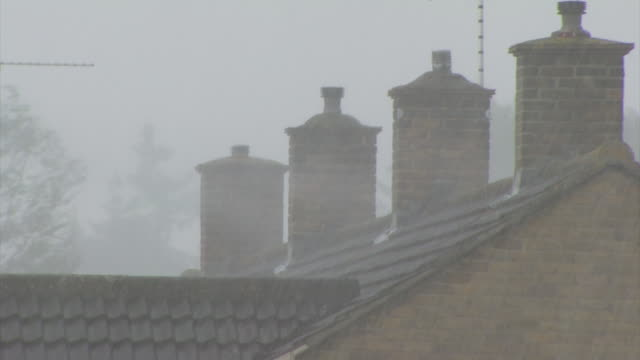 Torrential rain driven by strong winds blowing across roofs with chimneys, UK
