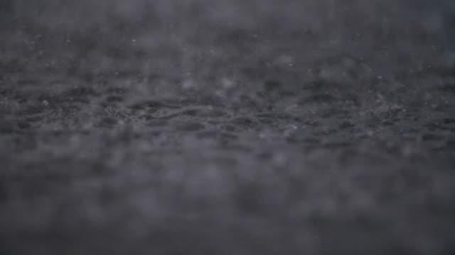 vídeos de stock, filmes e b-roll de chuva torrencial que cai no pavimento - nível da superfície