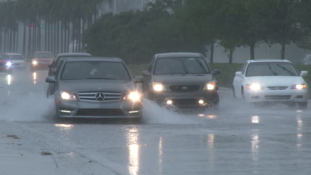 torrential rains from a summer thunderstorm in south florida create flash flooding conditions as motorists attempt to navigate deep water on local... - hialeah stock videos & royalty-free footage