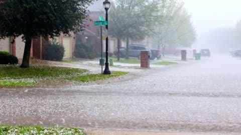 stockvideo's en b-roll-footage met stortregen met hagel in urban residential street - day