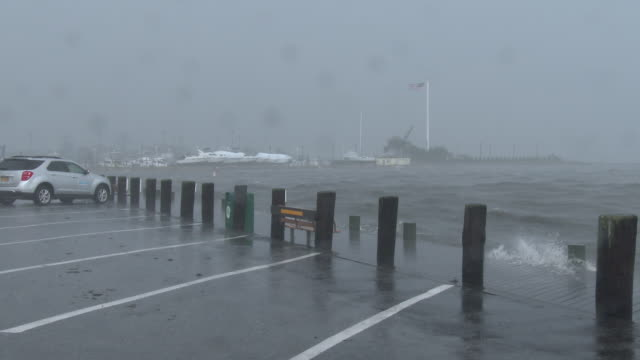 Torrential windswept rain falls and rough surf over washes a dock at a marina on Long Island during a sudden rain storm