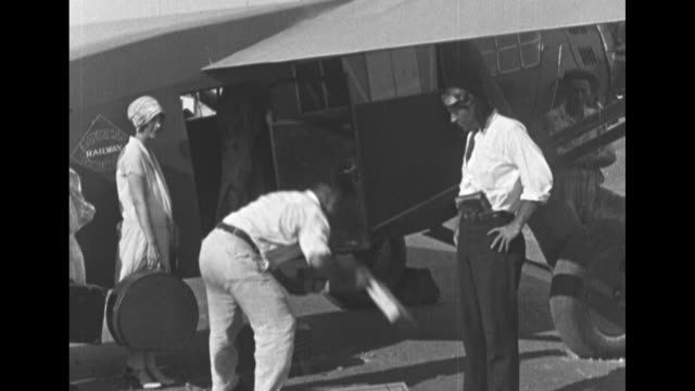 torrey webb being presented with flowers after landing in philadelphia / row of airmail biplanes men stuffing mail bags into the planes seaplane... - 複葉機点の映像素材/bロール