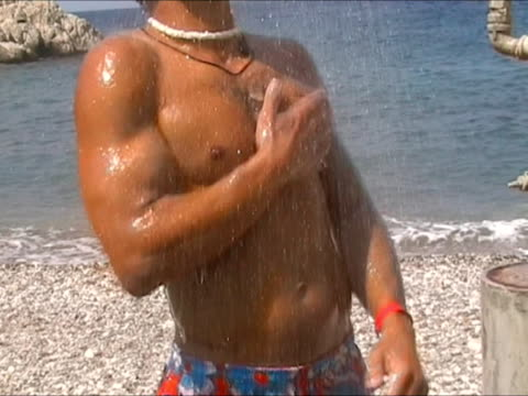 torso of young man having shower at the beach - torso stock videos & royalty-free footage