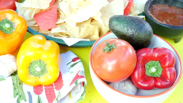 tortilla chips and salsa on table with fresh peppers, tomatoes, and other mexican cuisine ingredients. - mexican restaurant stock videos & royalty-free footage