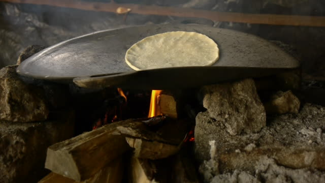 a tortilla is prepared over a fire. - tortilla flatbread stock videos & royalty-free footage