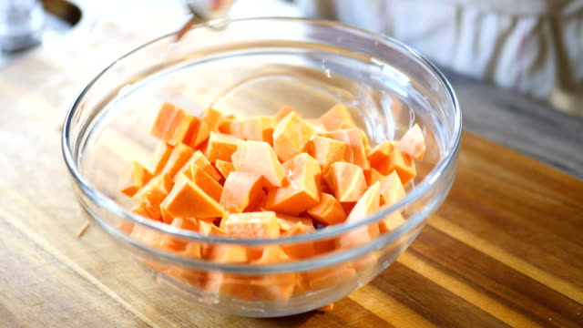tossing diced sweet potato with oil and seasoning - sweet potato stock videos & royalty-free footage